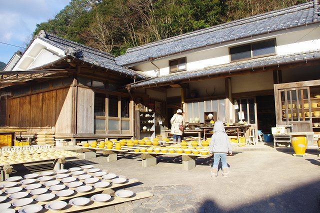 This is an Onta Ware workshop in the village of Onta, Oita, Japan. In the front yard of the workshop, a lot of formed bowls are drying in the sun on wooden boards. Families are visiting the workshop.