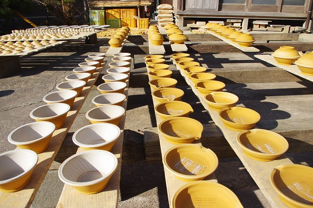 This is an Onta Ware workshop in the village of Onta, Oita, Japan. In the front yard of the workshop, a lot of formed bowls are drying in the sun on wooden boards.