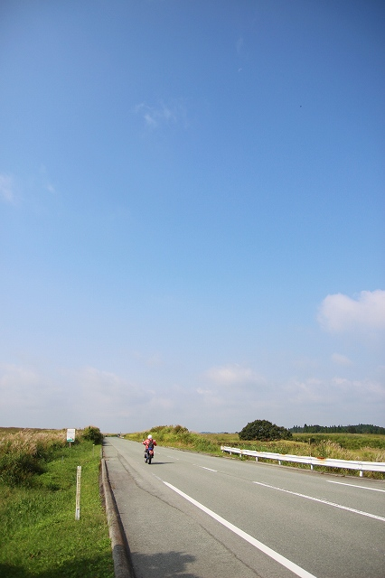 The Yamanami Highway is a road that connects Yufuin in Oita to Aso in Kumamoto in Japan. Under the blue sky, a motorcycle is riding along a straight road in the grassland.