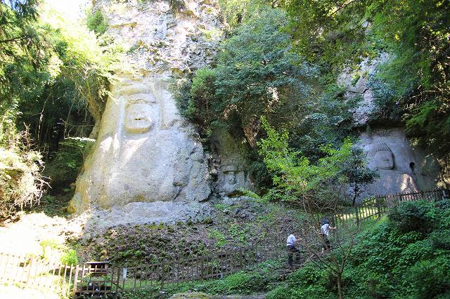 This is the Kumano Magaibutsu Buddha located on the Kunisaki Peninsula in Oita, Japan. Two large Magaibutsu are carved into the rock face. Two worshippers are climbing up the mountain path.
