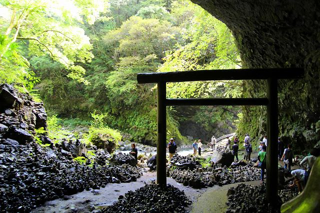 This is Amanoyasugawara riverbank in Takachiho, Miyazaki, Japan. There is a large cave with a torii gate and many piled up stones.