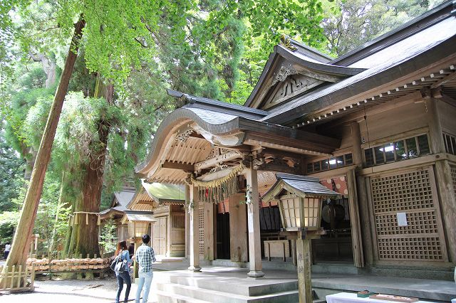 This is the divine wooden Takachiho Shrine in MIyazaki, Japan. Two worshippers are standing in front of the Takachiho Shrine.