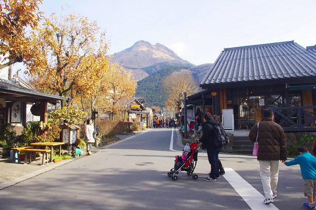 This is Yunotsubo Street in Yufuin, Oita, Japan. Both sides of the street are lined with stores and restaurants where tourists enjoy strolling. Mt. Yufudake is in the background.