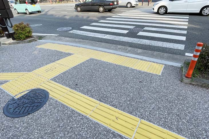 """There is a yellow block on the sidewalk in front of the crosswalk in Japan. These are called """"Braille blocks,"""" which are guides for the visually impaired."""