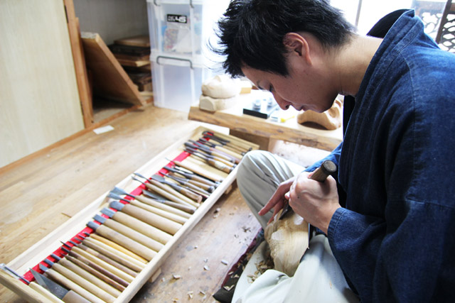 A traditional craftsman is carving Takachiho Kagura Masks.