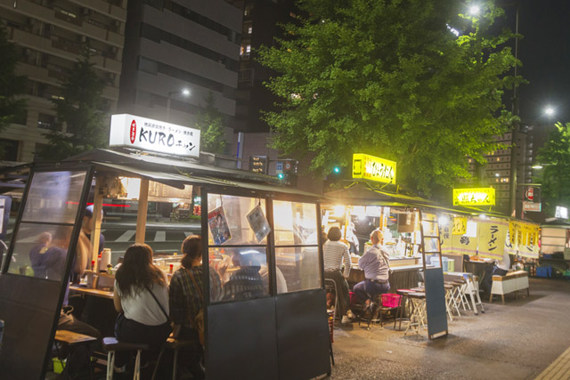At night, there are several food stalls lined up on the sidewalk in Fukuoka, Japan. Customers inside the stalls are enjoying eating and drinking.