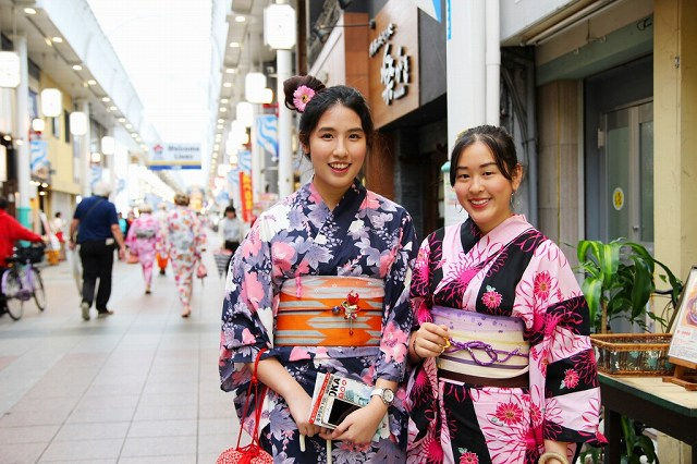 This is a picture of two smiling women in kimonos that are brightly colored, such as pink on a black background, pink or light purple on a dark blue background, and appropriately fitted with obi and obijime. This image is also linked to the Fukuoka Kimono Dress Up page on the website of Fukuoka Walks.