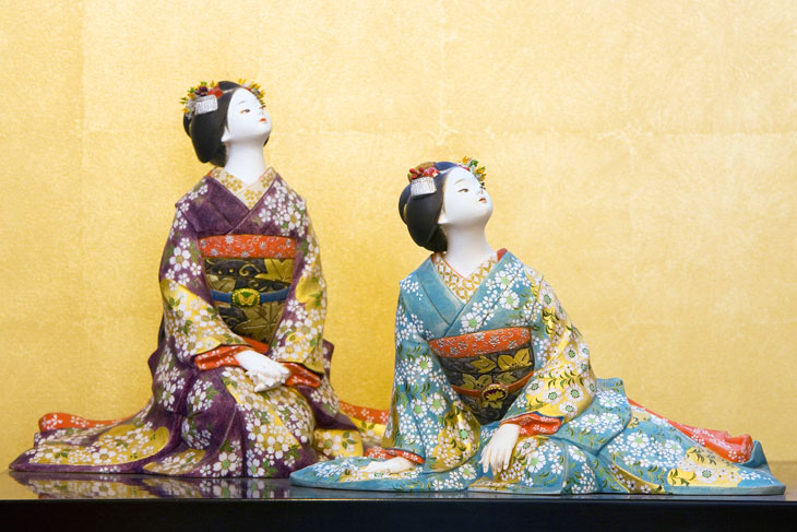 This is a picture of a Hakata doll with two women wearing colorful kimonos.