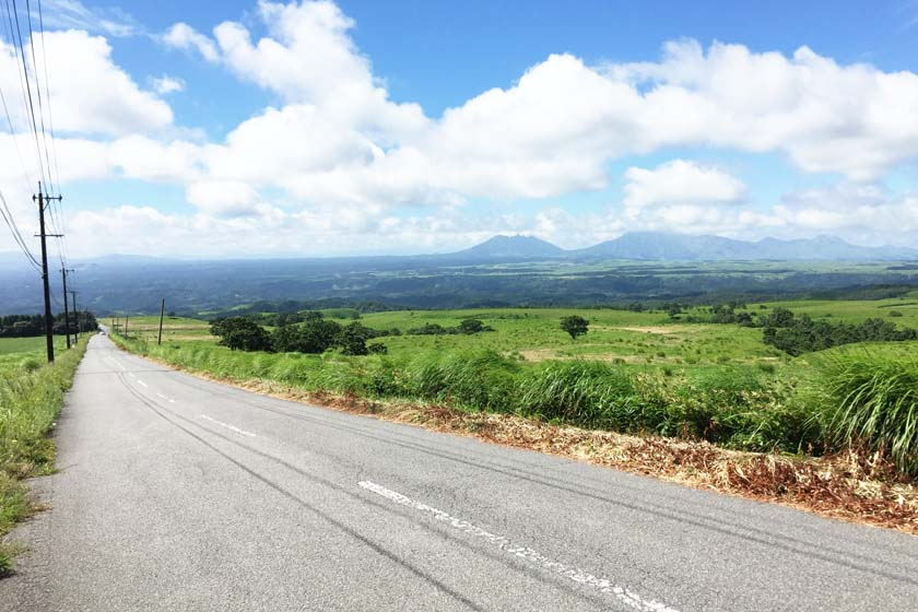 A straight road with a view of Mt. Aso from Kuju Highland.