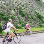 Two men participating in a bike tour organized by Trip Insight are riding their bicycles in front of a large stone wall in the Fukuoka Castle ruins in Fukuoka City, Japan.