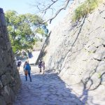This is a photo of the inside of Fukuoka Castle in Fukuoka City, Japan. Several people are walking along a cobblestone path between high stone walls. This image is also linked to the Fukuoka Castle Live Online Walking Tour page.