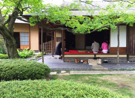 This is a picture of a Japanese garden in Fukuoka City, Japan. A tea ceremony is being held in a Japanese-style room in the garden. The greenery of the garden is beautiful. This image is also linked to the Japan Online Study Tours page.