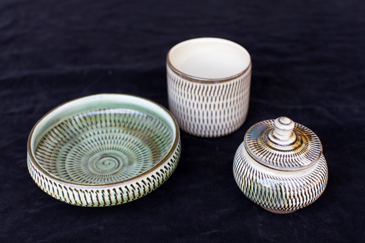 This is a photo of Kogata pottery made using traditional methods. There are three pieces in a row: a small plate, a teacup, and a small jar with a lid.