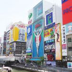 This is a picture of Dotonbori, a popular place in Osaka, Japan. The buildings along the river are lined with large colorful signs, and many tourists are taking pictures of them.