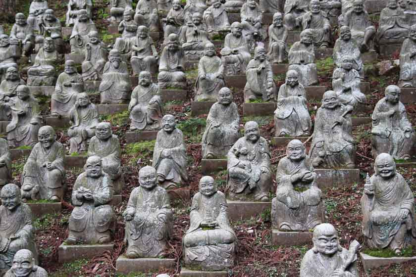 There are many Buddha statues lined up on the slope. Each one has a different expression on its face. This is called five hundred statues of arhats (Gohyakurakan zo), and it is located at Raizan Sennyoji Temple in Fukuoka.