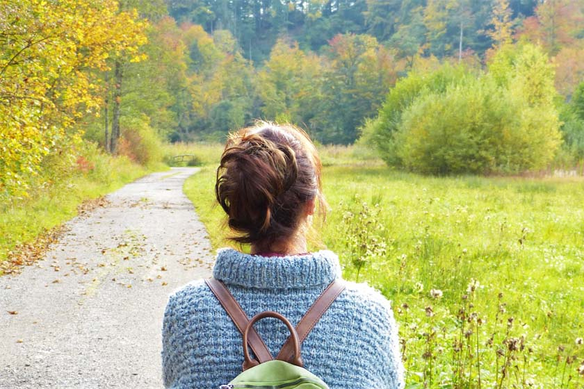 A woman traveling alone in Japan takes a pleasant stroll through a beautiful forest.