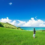 A traveler standing in the middle of a grassy field in Okinawa, Japan, looking across the field at the view of the ocean and white clouds on the horizon. This image is also linked to the Self-Guided Japan Tours page.