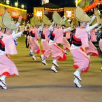 This is a picture of the Awa Odori dance, a festival held in Tokushima Prefecture in August. Women in peach-colored kimonos and straw-woven hats of unique semicircular shape are dancing with smiles on their faces.
