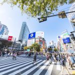 This is a photo of the scramble intersection in Shibuya, Tokyo, Japan, which is crowded with many young people. The intersection is surrounded by commercial buildings with billboards.